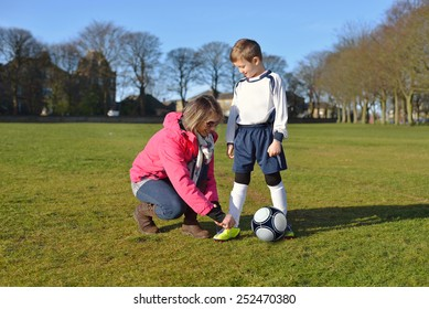 Mother with young  boy tying football boot laces in park.