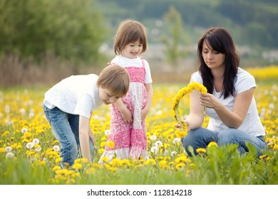 Mother and young children picking dandelion flowers  in a field.