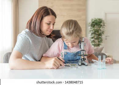 Mother and young daughter doing some experiments with microscope at home