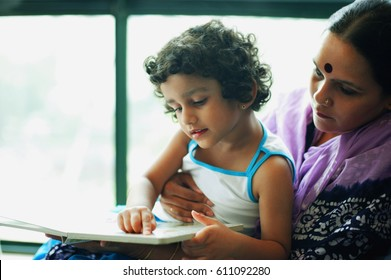 Mother and young daughter reading a book together