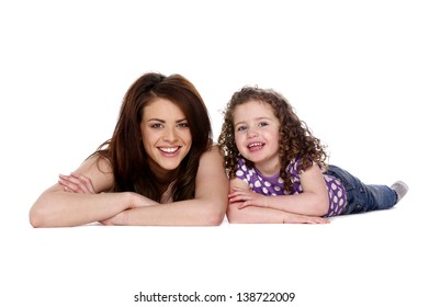 Mother and young daughter smiling at the camera isolated on a white background