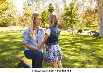 Mother and young daughter talking in a park, close up