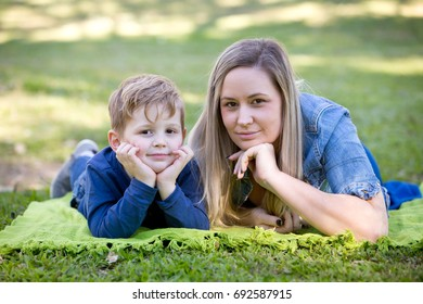 Mother and young son laying on blanket together in park - looking at camera