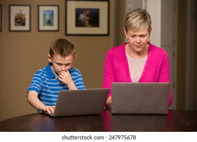 Mother and young son on computers.