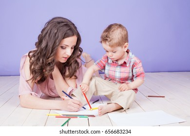 mother and young son play paint crayons