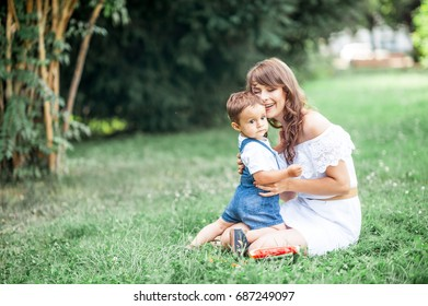 Mother and young son played on grass. Mom and young son eating watermelon. Picnic. Summer.