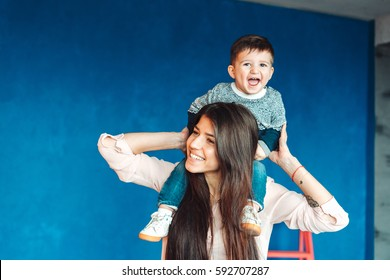 Mother and young son posing on wall background