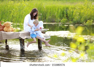 mother with a young son sitting by the lake with her �¢??�¢??bare feet in the summer