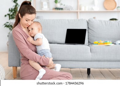 Mother-baby emotional attachment. Loving young mom hugging her adorable toddler son at home, sitting on floor in living room. copy space