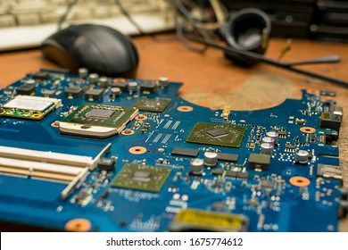 the motherboard from the computer lies on an old wooden worn-out repair table of the service center against the background of tools, a computer mouse and keyboard