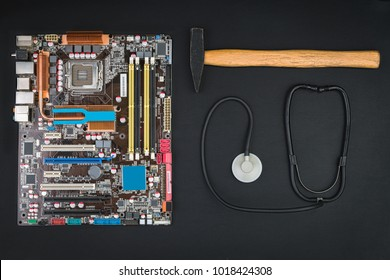 Motherboard, hammer and stethoscope on a black table. Repair or crash the computer.