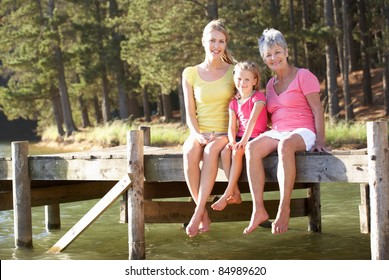 Mother,daughter and grandmother sitting by lake
