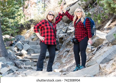A mother-daughter pair, wearing lumberjack buffalo plaid flannel shirts, give a high five after completing a challenging outdoor nature hike to Devil's Postpile National Monument in the Sierra Nevada