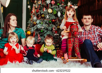 The mother,father and children sitting near Christmas Tree