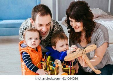 The mother,father and sons playing with toys