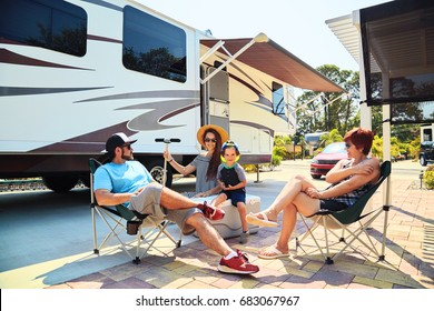 Mother,father,son and grandmother sitting near camping trailer,smiling.Woman,men,kid relaxing on chairs near car.Family spending time together on vacation in modern rv park
