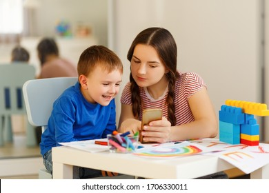 Motherhood concept. Brunette and son play with plastic building blocks. mom show somethimg funny in phone. Excited preschooler playing with his smiling mother or kindergarten teacher.