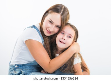 Motherhood, family and relationship concept - Happy mother and little daughter having fun on white background