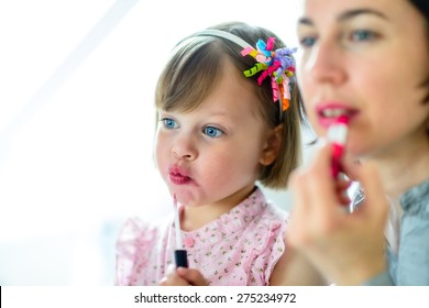 Motherhood. Little girl imitating her mother who is applying lipstick in front of a mirror.