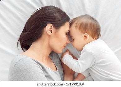 Motherhood. Mother and baby together holding hands sleeping lying on bed peaceful top view close-up