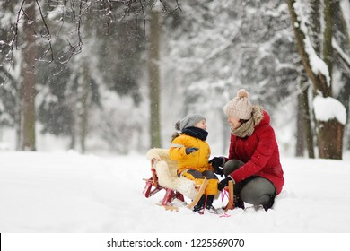 Mother/nanny talk with small child during sledding in winter park. Family winter activities outdoors.