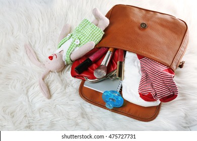 Mothers bag with accessories on carpet