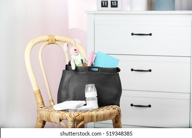 Mothers bag with accessories on chair