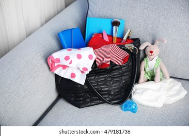 Mothers bag with accessories on couch