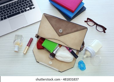 Mothers bag with accessories on table