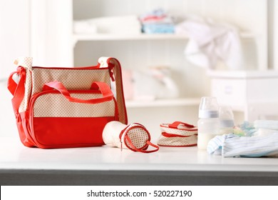 Mothers bag and accessories on table