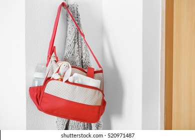 Mothers bag with toy and accessories hanging on wall hook
