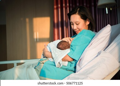 Mothers breastfeed while dating a beautiful golden sunset, golden light shines on the mother and child.