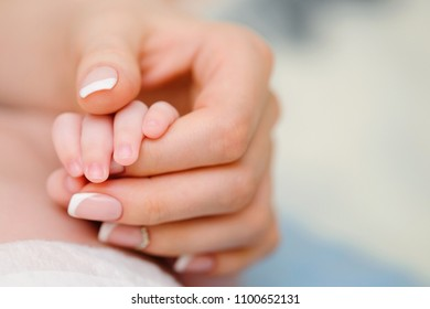 Mother's caring hand holding her little baby's hand with love. Infant body parts closeup. Children's day