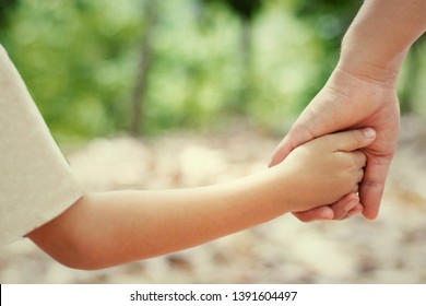 Mother's and child hold hands. Happy in the garden. Mother's love in the hand, on the palm.