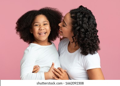 Mother's Daughter. Portrait Of Cute Little Afro Girl With Her Happy Mom Cuddling And Posing Together On Pink Background In Studio