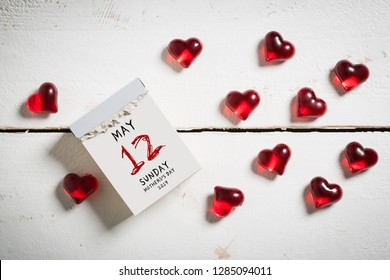 Mother's Day 2019, tear-off calendar with 12th of may on top, surrounded by hearts on a wooden surface