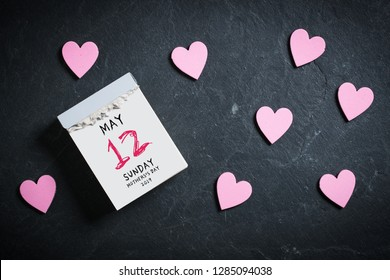 Mother's Day 2019, tear-off calendar with 12th of may on top, surrounded by hearts on slate background