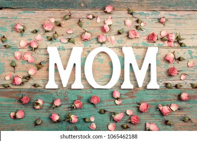 Mothers day background with letters and small pink roses on old wooden table. Happy mother's day concept.