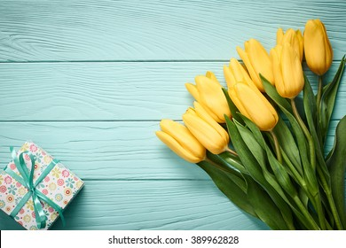 Mothers Day background. Tulips bouquet and gift box on blue wood. Beautiful spring yellow flowers. Still life,Flat lay. Unusual creative holiday greeting card Minimal