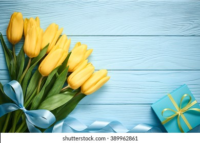 Mothers Day background. Tulips bouquet and gift box on blue wood. Beautiful spring yellow flowers. Still life,Flat lay. Unusual creative holiday greeting card