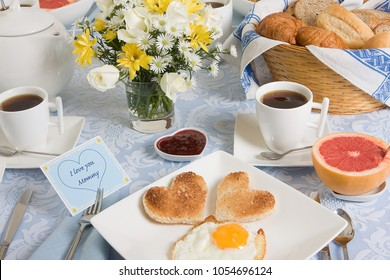 Mother's day breakfast table with eggs and toast in heart shape