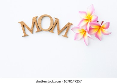 Mother's day card concept idea, wood design text with fresh colorful Plumeria flower with space on white paper texture background