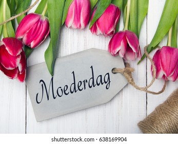 Mother's day card  with Dutch words: Mother's day. Tulip bouquet on white wooden background, copy space