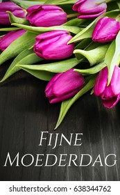 Mother's day card  with Dutch words: Happy Mother's day, and tulip bouquet on black wooden background