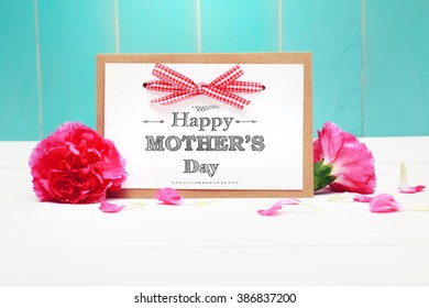 Mothers day card with pink carnations over teal wooden wall