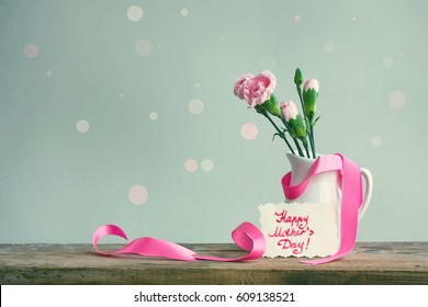 """Mother's day card, pink carnations in a white vase with ribbon on a wooden table, note with the inscription """"happy mother's day"""", gray background"""