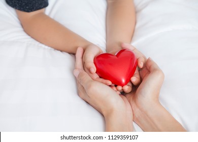 Mother's Day celebration with woman holds young kid's hands supporting red heart gift, and charity donation for nursing children concept.