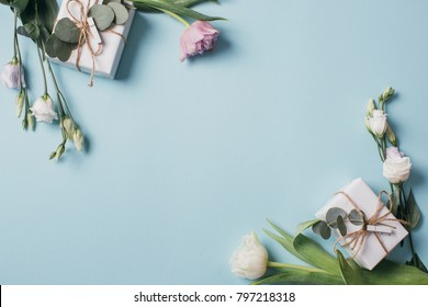 Mother's Day Composition: Eustoma, eucalyptus, tulips and a gift boxes on a blue background. Top view.Flat lay.