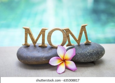 Mother's day concept background, mom wooden text on spa stone with space on blurred swimming pool background