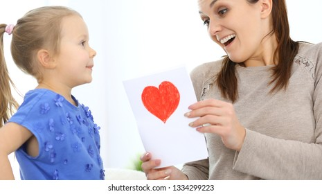 Mother's day concept. Child daughter congratulates mom and gives her postcard with red heart shape. Mum and girl happy smiling and hugging. Family fun and holiday